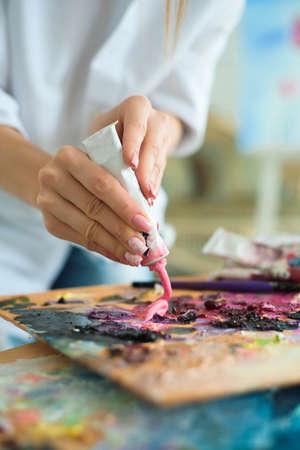 Foto de Art, creativity and people concept - close up of artist with palette knife painting still life on easel at studio. - Imagen libre de derechos
