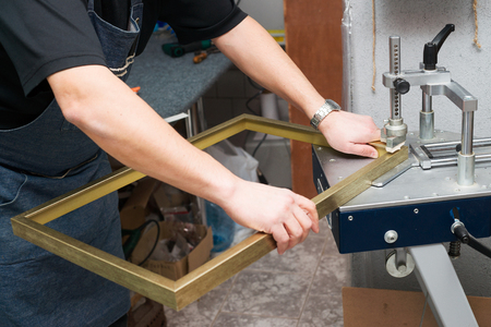 Photo pour Craftsman working on frame in frameshop. Professional framer hand holding frame angle. Top view. - image libre de droit