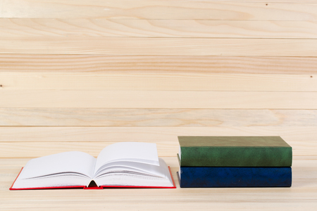 Open book, stack of hardback books on wooden table. Back to school. Copy space.