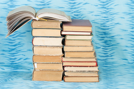 Open book, stack of hardback books on blue cloth. Back to school. Copy space