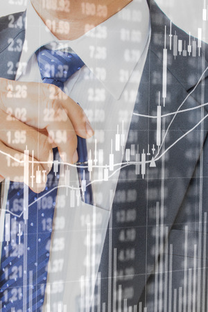 double exposure of stock market graph on  business man pulling or putting blue pen in his pocket as background