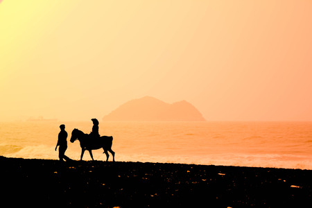 Photo pour silhouette Dad walking with daughter riding on horse on the beach - image libre de droit