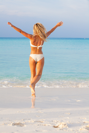 Blonde young girl dancing on the beach