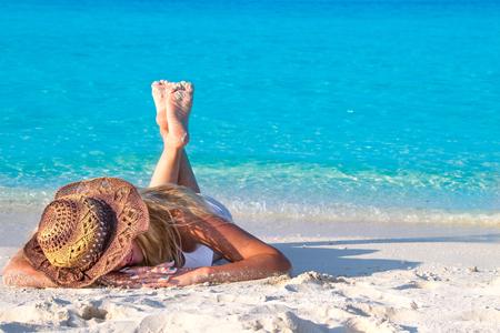 Photo pour Blond woman lies with hat on the sandy beach - image libre de droit