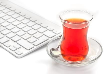 White keyboard and turkish tulips tea glass