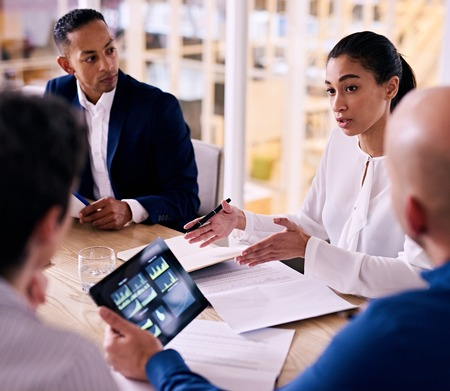Foto de square image of confident young female corporate executive busy giving an explanation for her proposal to expand the firm with one other member looking at financial graphs on his tablet. - Imagen libre de derechos