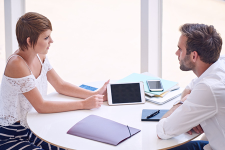 Young female creative showing a business presentation to a potential male business investor on her electronic tablet while seated at a round table in a bright local co-work space.