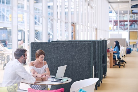 Large open indoor co-working space that is light and bright with man and woman busy meeting each other in the foreground of the image on one of the round tables in the office space.