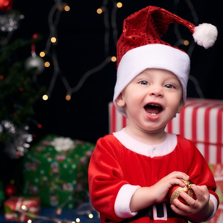 Baby boy wearing a Santa Clause outfit and smiling joyfully at the camera while holding a christmas decoration and sitting in front of the decorated tree and presents.