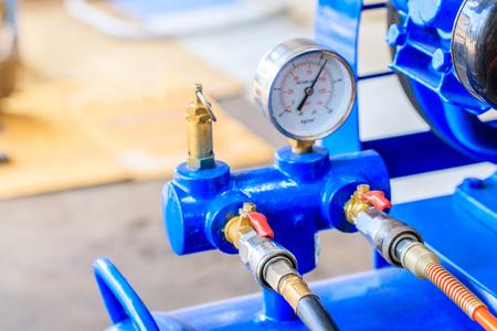 Air pump and pressure gauge in motorcycle repair shop.