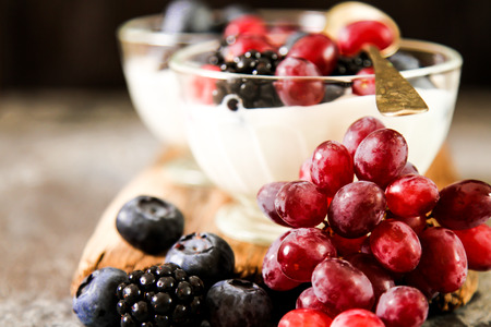 Serving of white Yogurt with Whole Fresh Blueberries  on Old Rustic Wooden Table. Closeup Detail.