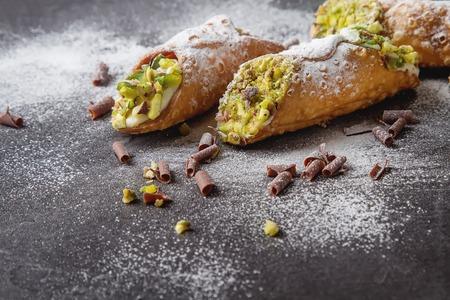 Foto de Sweet homemade cannoli stuffed with ricotta cheese cream and pistachial Sicilian dessert. Italian pastry. - Imagen libre de derechos