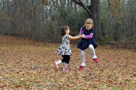 Two friends dance for joy in the Autumn leaves in Arkansas.  They are holding hands and jumping high and running in circles.