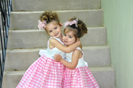 Two sisters dressed identically embrace on Easter Sunday morning   They are both smiling and happy