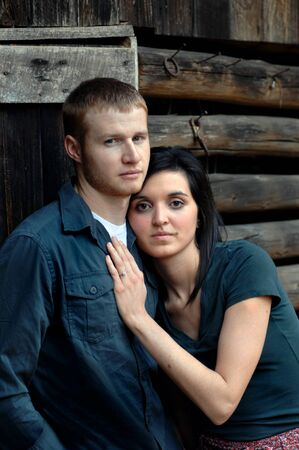Young man and woman rest against a rustic, wooden, log cabin   Both are serious and look solemnly at the camera
