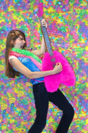Getting into the part, teen plays wildly on the guitar, grimacing to the 70s disco beat.  Pink guitar with tye-dye background.