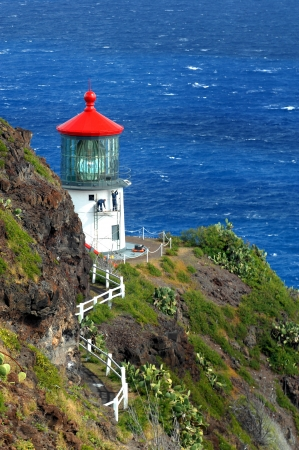 Two workmen paint the exterior of the Makapuu Point Lighthouse on the Island of Oahu, Hawaii.  Damages from wind and rain have eroded the exterior of the historic landmark.