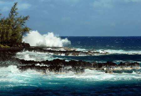 Waves crash wildly on the rocky shoreline on the Big Island of Hawaii   Black lava beach near south of McKinzie Beach Park