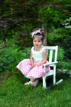 Little girl poses on a white, wooden rocking chair   She is dressed in her Easter outfit and is smiling happily   Spring green surrounds her outdoors