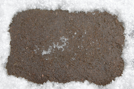 Frame shows a background edging of snow.  Center is wet pavement.
