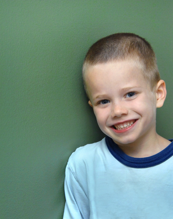 Smiling and happy young boy leans against a green wall in his home.