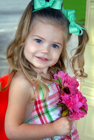 Beautiful little girl holds a bouquet of pink Azaleas.  Her hair hangs in curls around her head.  Little green bows decorate her hair.  She is smiling sweetly.