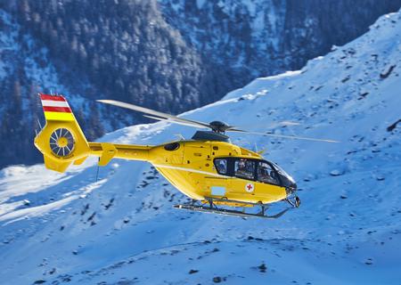 Foto de yellow helicopter on the background of snowy mountains - Imagen libre de derechos