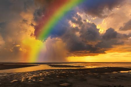 Sunset with rainbow and rainy over the beach.