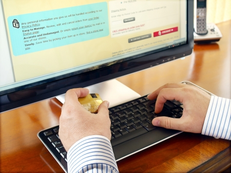 Businessman with credit card using computer for online purchase.