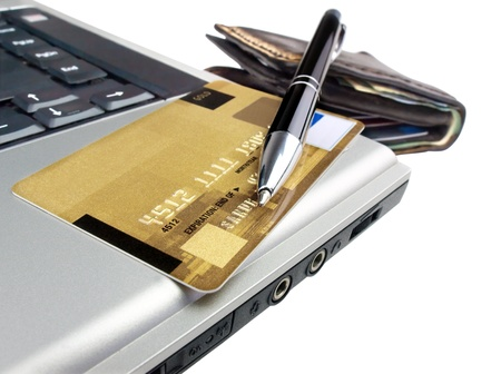 Credit card with pen on laptop ready for online purchase. Isolated.