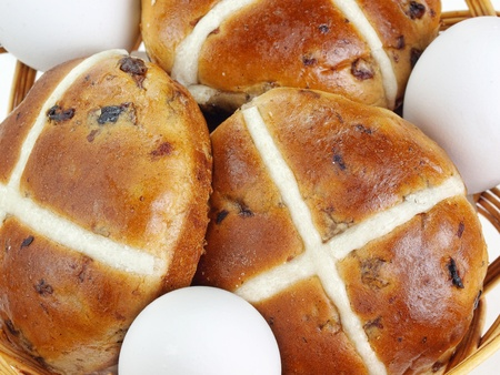 Closeup of basket with fresh hot cross buns and eggs