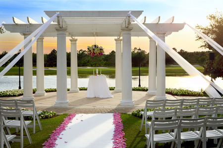 Wedding gazebo on a lake shore in the park at the sunset
