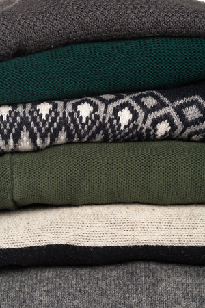 Winter and fall cozy sweaters stack, woolen sweaters and blankets still life with air freshener
