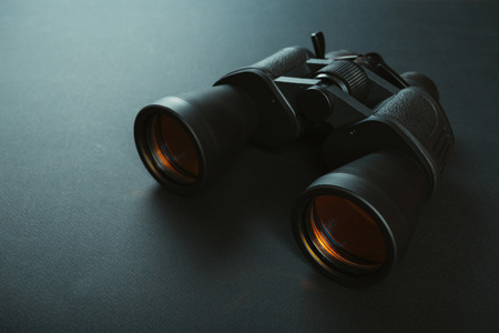 Photo for Black binoculars with orange lens on dark background - Royalty Free Image