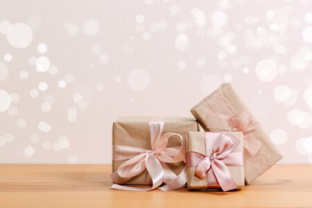 set of beautiful different gift boxes made by handmade with pink bows on a wooden table with a light background
