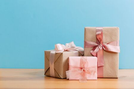 set of beautiful different gift boxes made by handmade with pink bows on a wooden table with a blue background