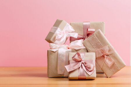set of beautiful different gift boxes made by handmade with pink bows on a wooden table with a pink background