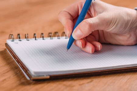 Photo pour Close up of woman's hands writing in spiral notepad placed on wooden desktop - image libre de droit