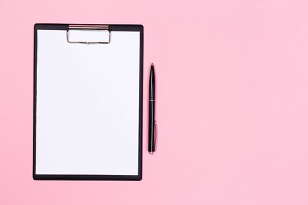 Photo for Clipboard with white sheet and pen on a colored background. View from above. space for text - Royalty Free Image