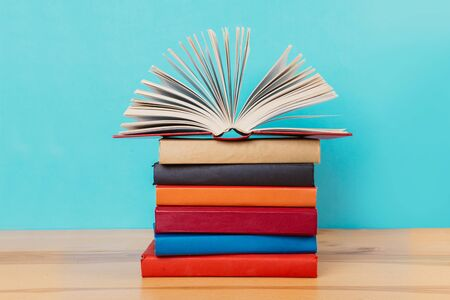 Photo for A simple composition of many hardback books, raw books on a wooden table and a bright blue background. Going back to school. Copy space. Education. - Royalty Free Image