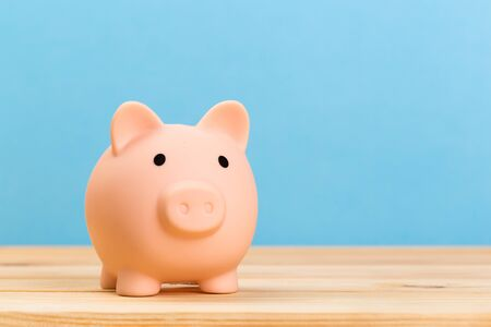 Photo pour Pink piggy bank on wooden table and blue background. The concept of storage, accumulation. Crisis, inflation, financial collapse. - image libre de droit