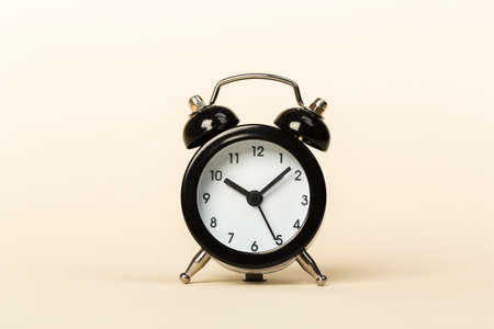 black retro alarm clock on a beige background, concept of time, daily routine. ten hours 10 minutes