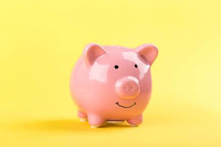 Photo pour pink piggy bank on a yellow background. - image libre de droit