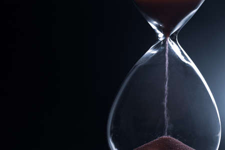 Photo pour Sand passes through hourglass bulbs measuring the transit time counting down to the deadline, against a dark background - image libre de droit