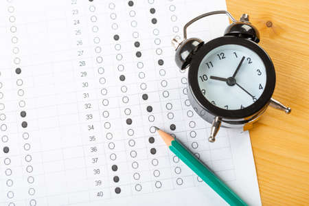 Photo pour answer sheet, test in exercise and passing examination paper computer sheet with pencil alarm clock and pencil for education concept - image libre de droit