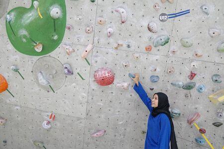 Photo pour A muslim woman and wall climbing activity - image libre de droit