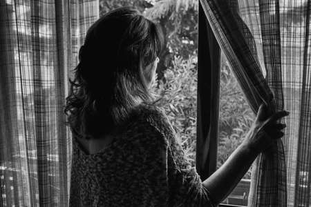 Photo pour Rear view of a pretty young woman standing in the doorway on the balcony and looking outside into the street - image libre de droit