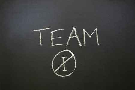 A horizontal color photograph of the statement No I in Team written on a chalkboard.