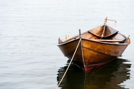 Old wooden row boat on water