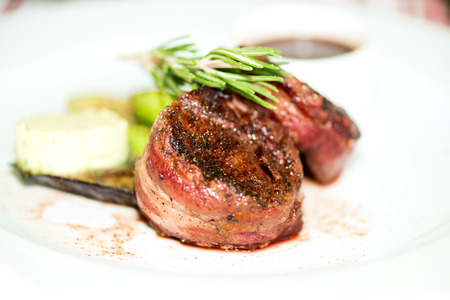Grilled fillet mignon steak wrapped in bacon, with grilled vegetables and rosemarin